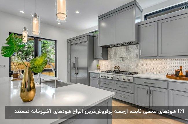 آشپزخانه ای با کابینت های طوسی، کفپوش رنگ چوب و کابینت هود مخفی ثابت