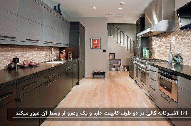 پلان گالی آشپزخانه ای با با بین کابینتی و کفپوش قهوه ای روشن و کابینت های مشکی و خاکستری