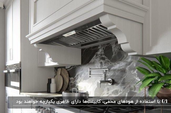 آشپزخانه ای با کابینت های سفید، بین کابینتی طوسی و کابینت هود مخفی