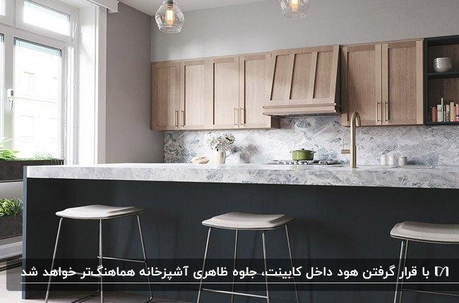 آشپزخانه ای با کابینت های رنگ چوب و خاکستری به همراه کابینت هود مخفی