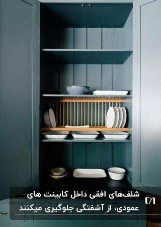 آشپزخانه ای با کابینت های سبز تیره و شلف افقی داخل کابینت چوبی