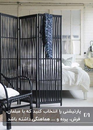 پارتیشن متحرک مشکی رنگ در اتاق خوابی با تخت دو نفره سفید و صندلی راحتی با فریم مشکی