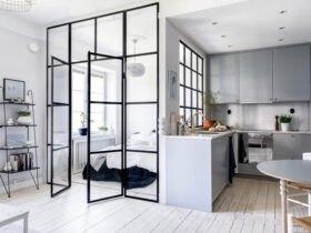 آپارتمان کوچکی با کابینت های طوسی و اتاق خوابی که با پارتیشن شیشه ای فریم دار از پذیرایی جدا شده