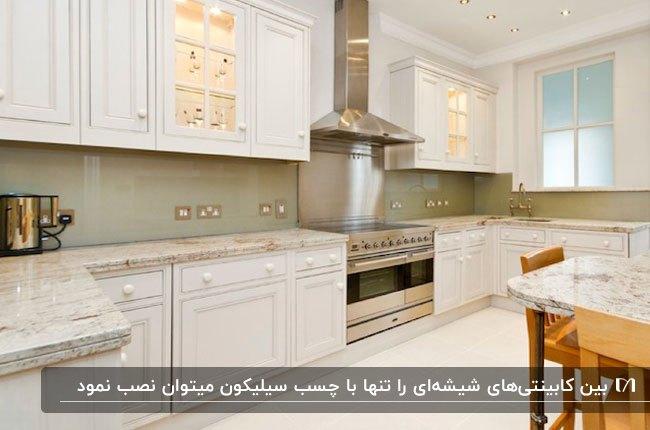 آشپزخانه ای با کابینت های کلاسیک سفید و بین کابینتی شیشه ای صدری رنگ