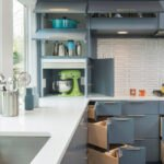 آشپزخانه ای با کابینت های طوسی، صفحه رویی کابینت سفید و کابینت گوشه کشویی