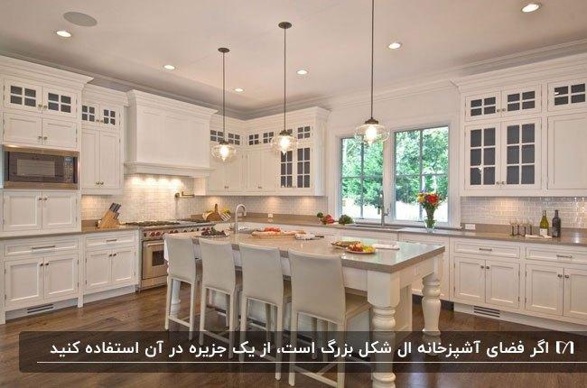 پلان ال شکل آشپزخانه ای کلاسیک با کابینت ها و جزیره سفید و سه لوستر آویز