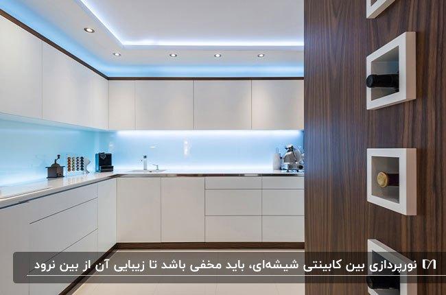 آشپزخانه ای با کابینت های سفید و کتیبه های چوبی قهوه ای، بین کابینتی شیشه ای آبی آسمانی و نورپردازی مخفی