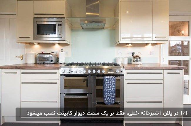 پلان خطی آشپزخانه با کابینت های های گلاس سفید و دستگیره های نقره ای