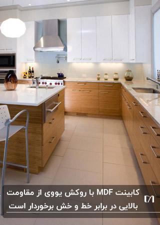 آشپزخانه ای با کابینت MDF و روکش یووی با ترکیب رنگ چوب و سفید با دستگیره های فلزی نقره ای