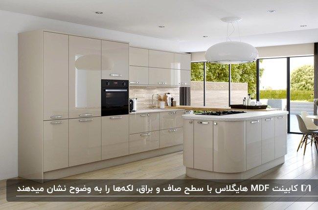 آشپزخانه ای با کابینت و جزیره منحنی از جنس MDF با روکش هایگلاس کرم رنگ و لوستر آویز سفید