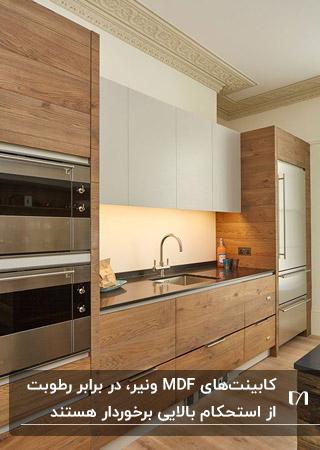 آشپزخانه ای با کابینت MDF و روکش ونیر طرح چوب و ترکیب آن با رنگ کرم و نورپردازی مخفی زیر کابینت