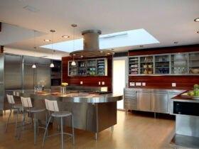 آشپزخانه ای بزرگ با کابینت فلزی، جزیره و صندلی های فلزی و بین کابینتی قهوه ای