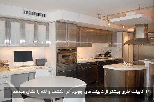 آشپزخانه ای با کابینت فلزی، درب های فلزی و شیشه ای، میز و صندلی های غذاخوری سفید