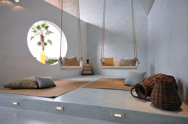 اتاقی با کفپوش و دیوارپوش میکروسمنت، دو تاب، سبد حصیری و پنجره دایره