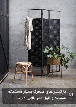 پارتیشن متحرک مشکی در اتاقی با دیوارهای سیمانی کنار چهارپایه چوبی و گلدان