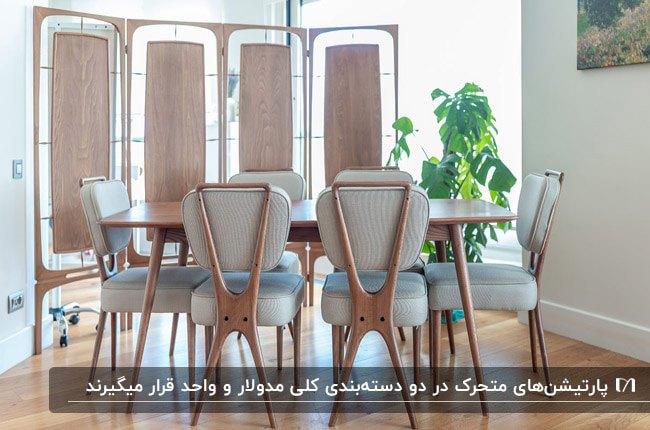 اتاق غذاخوری با میز چوبی و صندلی های طوسی و پارتیشن چوبی متحرک