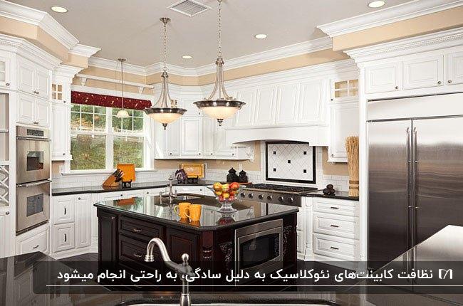 آشپزخانه با کابینت نئوکلاسیک سفید و جزیره قهوه ای و دو لوستر آویز