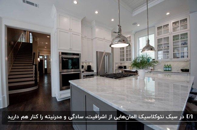 آشپزخانه ای با کابینت نئوکلاسیک به رنگ سفید و طوسی با کفپوش قهوه ای تیره