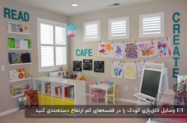 اتاق بازی کودک با قفسه های دیواری سفید، تخت یاه پایه دار کوچک و نقاشی های کودک روی دیوار