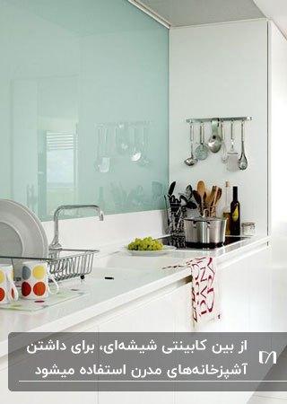 آشپزخانه کوچکی با کابینت های سفید و بین کابینتی شیشه ای سبزآبی روشن