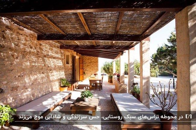 تراسی به سبک روستایی با نیمکت و میز و صندلی های چوبی و سقف حصیری