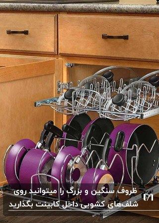 آشپزخانه ای با کابینت های چوبی قهوه ای، شلف داخل کابینت کشویی و قابلمه های بنفش