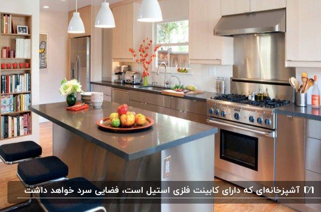 آشپزخانه ای با کابینت فلزی استیل، چهارپایه های کانتر مشکی و سه لوستر آویز