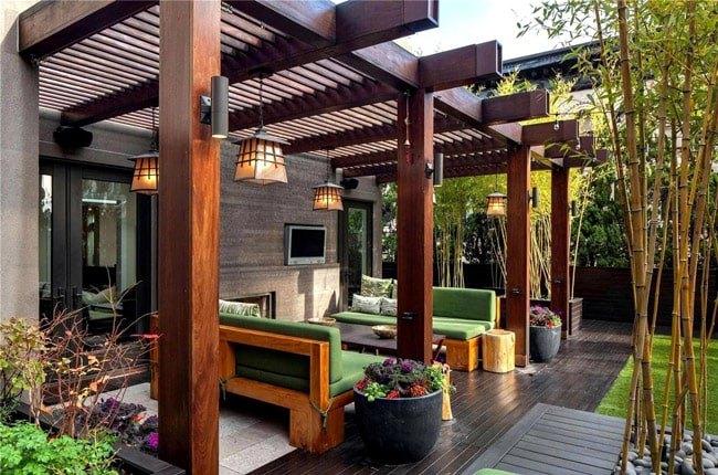 تراسی با دیوار و تیرهای سقف چوبی به همراه مبلمان راحتی با فریم چوبی و پارچه سبز رنگ