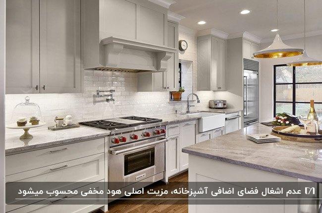 آشپزخانه ای با کابینت های سفید، هود مخفی و نورپردازی هالوژن