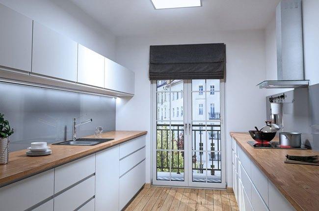 آشپزخانه ای با کابینت های سفید، صفحه رویی کابینت و کفپوش رنگ چوب و بین کابینتی شیشه ای طوسی رنگ