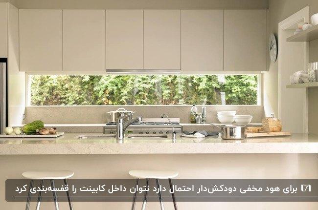 آشپزخانه ای با کابینت خطی کرم رنگ و کابینت هود مخفی و پنجره بین کابینتی