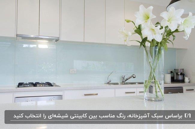 آشپزخانه ای با کابینت ها و جزیره سفید و بین کابینتی شیشه ای آبی روشن