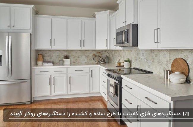 آشپزخانه ای با کابینت های سفید و پارکت چوبی به همراه دستگیره های فلزی به عنوان اجزای اصلی کابینت