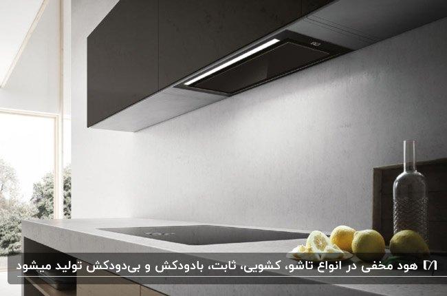 آشپزخانه مدرنی با کابینت های تیره و کابینت هود مخفی