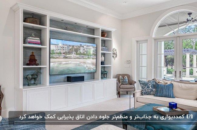 اتاق پذیرایی با مبل کرم رنگ، کوسن های طرحدار آبی و سفید و کمد دیواری سفید