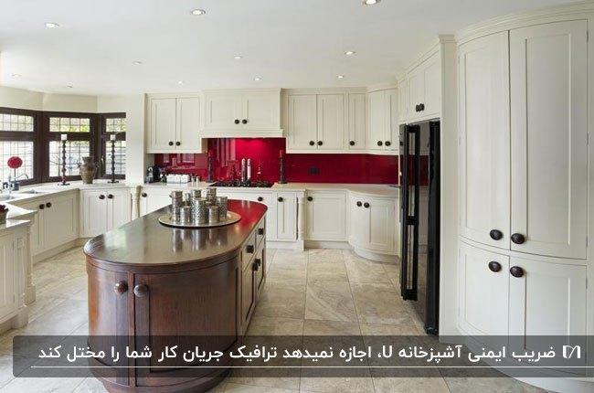 پلان یو شکل آشپزخانه با کابینت های کرم رنگ، جزیره قهوهای و کاشی بین کابینتی قرمز رنگ