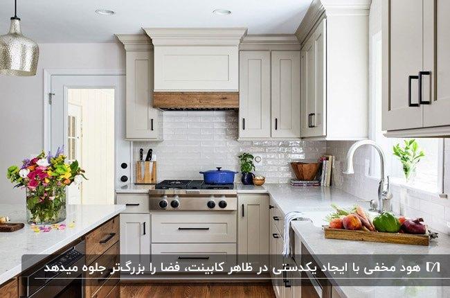 آشپزخانه ای با کابینت های ال شکل و جزیره کرم رنگ به همراه کابینت هود مخفی