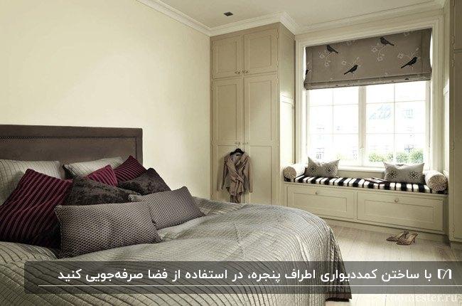 اتاق خوابی با تخت دو نفره طوسی و خاکستری و کمد دیواری کرم رنگ اطراف پنجره مربعی