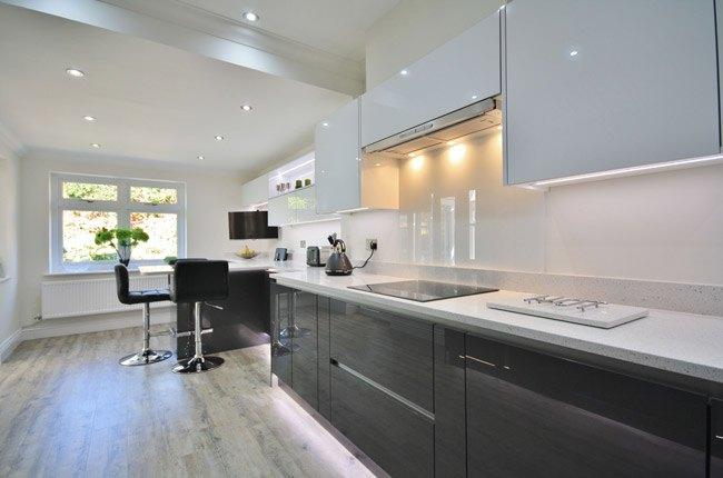 آشپزخانه ای با کابینت های گلاس سفید و مشکی و کابینت هود مخفی