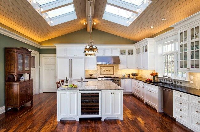 آشپزخانه ای با کفپوش پارکت قهوه ای، پنجره های سقفی و کابینت نئوکلاسیک سفید