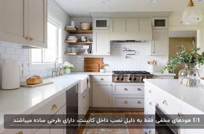 آشپزخانه ای با کابینت ال شکل کرم، هود مخفی و کفپوش پارکت