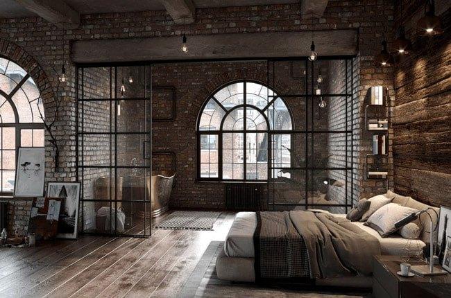 اتاق خواب بزرگی با دیوارهای آجری، تخت دو نفره و پارتیشن متحرک شیشه ای برای جدا کردن حمام