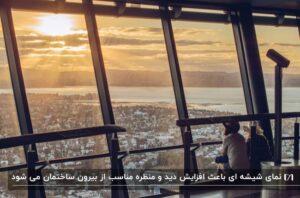 دو دختر در حال تماشای منظره ی شهر و غروب آفتاب از یک برج با نمای شیشه ای