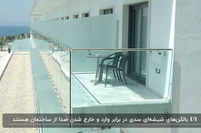 ساختمانی با نمای سفید رنگ و بالکن شیشهای و میز و صندلی های راحتی مشکی