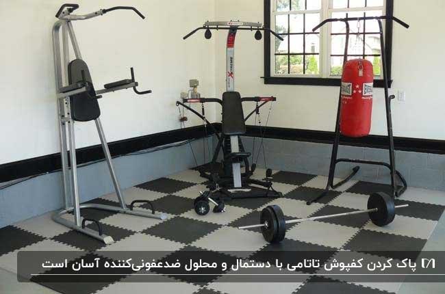 سالن ورزشی با دستگاه های ورزشی و چگالی کفپوش تاتامی طوسی و خاکستری