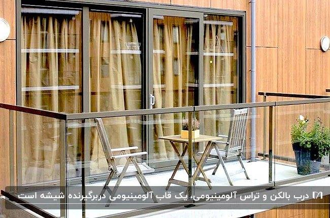 تراس و بالکن کوچکی با میز و صندلی چوبی، حفاظ و درب شیشه ای با فریم آلومینیومی قهوه ای