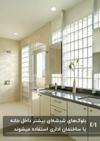 حمام و سرویس بهداشتی با کابینت های کرم رنگ، دیوار جدا کننده شیشه ای و دیوار بلوک شیشه ای