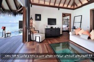 اتاقی با کفپوش شیشه ای و پارکت چوبی، مبلمان سفید و میز کنسول مشکی