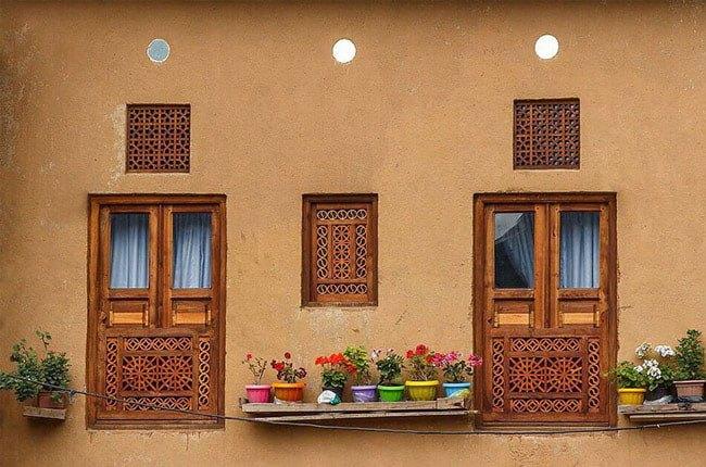 خانه ای با نمای گلی و درب و پنجره های چوبی گره چینی کار شده و گلدان های گل رنگی