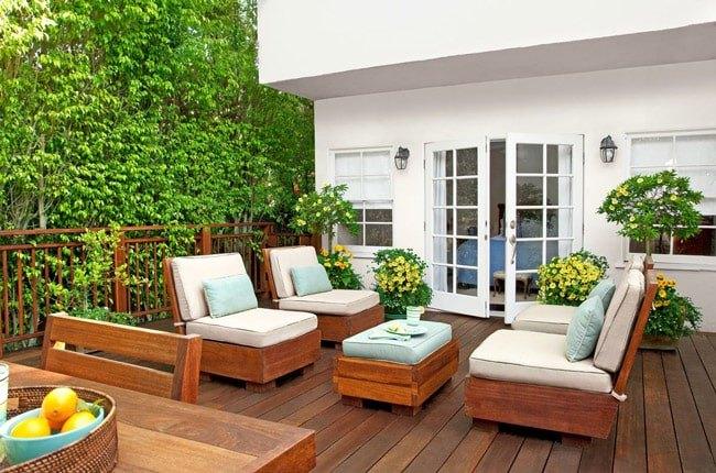 تراس و بالکن با دیوار سبز، کفپوش و مبلمان چوبی با پارچه سفید و درب تراس با فریم سفید